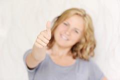 Giovane donna sorridente che mostra i pollici su Fotografia Stock Libera da Diritti