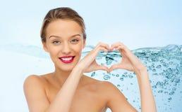 Giovane donna sorridente che mostra il segno della mano di forma del cuore Fotografia Stock