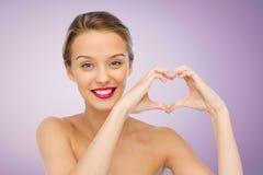 Giovane donna sorridente che mostra il segno della mano di forma del cuore Fotografie Stock Libere da Diritti