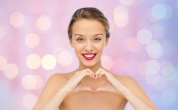 Giovane donna sorridente che mostra il segno della mano di forma del cuore Immagini Stock Libere da Diritti