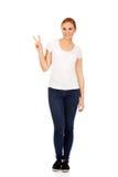 Giovane donna sorridente che mostra il segno di vittoria Immagine Stock