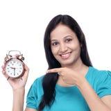 Giovane donna sorridente che mostra sveglia antica Immagine Stock