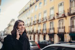 Giovane donna sorridente che parla sul suo smartphone sulla via Comunicando con gli amici, liberi le chiamate ed i messaggi per i fotografia stock libera da diritti