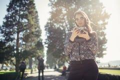 Giovane donna sorridente che parla sul suo smartphone sulla via Comunicando con gli amici, liberi le chiamate ed i messaggi per i fotografia stock