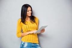 Giovane donna sorridente che per mezzo del computer della compressa Fotografia Stock