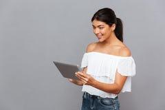 Giovane donna sorridente che per mezzo del computer della compressa Fotografie Stock