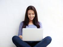 Giovane donna sorridente che per mezzo del computer portatile Fotografie Stock