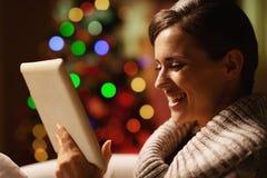 Giovane donna sorridente che per mezzo del pc della compressa davanti all'albero di Natale Fotografia Stock