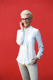 Giovane donna sorridente che per mezzo del telefono cellulare Immagini Stock