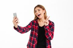 Giovane donna sorridente che per mezzo del telefono cellulare con le cuffie Fotografia Stock