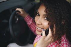 Giovane donna sorridente che per mezzo del telefono mentre conducendo la sua automobile immagini stock libere da diritti