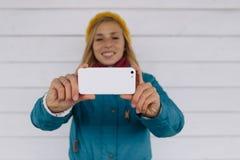 Giovane donna sorridente che per mezzo dello Smart Phone telefono cellulare di usi della donna per prendere foto Fotografia Stock