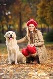 Giovane donna sorridente che posa con un labrador retriever   Fotografia Stock