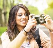 Giovane donna sorridente che prende le immagini. Fotografia Stock