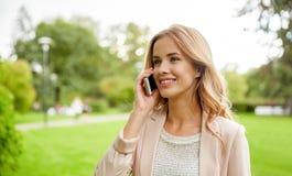 Giovane donna sorridente che rivolge allo smartphone all'aperto Fotografia Stock