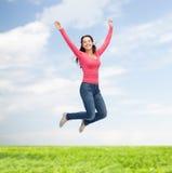 Giovane donna sorridente che salta in aria Immagini Stock
