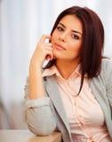 Giovane donna sorridente che si siede alla tavola Fotografie Stock
