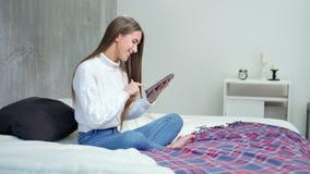 Giovane donna sorridente che si siede sul letto in pc della compressa della tenuta della camera da letto che gode e che si rilass video d archivio