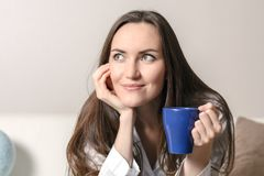 Giovane donna sorridente che si siede sul sofà nella stanza in pigiami blu con una tazza di tè ed il sogno circa il futuro Fotografie Stock Libere da Diritti