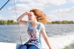 Giovane donna sorridente che si siede sulla barca a vela, godente della luce solare, crociera del fiume o del mare, vacanze estiv Immagini Stock