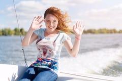 Giovane donna sorridente che si siede sulla barca a vela, godente della luce solare, crociera del fiume o del mare, vacanze estiv Fotografia Stock Libera da Diritti