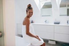 Giovane donna sorridente che si siede sulla vasca Fotografia Stock Libera da Diritti