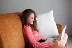 Giovane donna sorridente che si siede sullo strato che esamina computer portatile Fotografie Stock Libere da Diritti