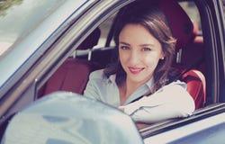 Giovane donna sorridente che si siede in un'automobile fotografie stock