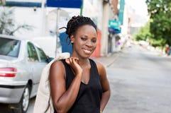 Giovane donna sorridente che sta e che esamina la macchina fotografica Fotografia Stock Libera da Diritti
