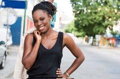 Giovane donna sorridente che sta e che esamina la macchina fotografica Immagine Stock Libera da Diritti