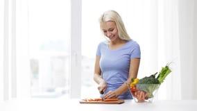 Giovane donna sorridente che taglia carota a pezzi a casa stock footage