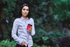 Giovane donna sorridente che tiene la tazza di caffè fotografie stock