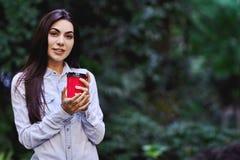 Giovane donna sorridente che tiene la tazza di caffè immagine stock