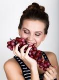 Giovane donna sorridente che tiene mazzo rosso fresco di uva Immagine Stock