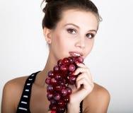 Giovane donna sorridente che tiene mazzo rosso fresco di uva Fotografia Stock Libera da Diritti