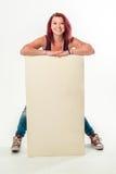 Giovane donna sorridente che tiene un'insegna bianca in bianco Fotografie Stock Libere da Diritti