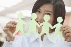 Giovane donna sorridente che tiene una catena delle figure taglio di carta e di esame della macchina fotografica Immagine Stock