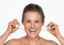 Giovane donna sorridente che usando le conchiglie come orecchini Immagini Stock