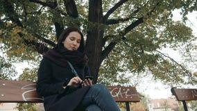 Giovane donna sorridente che utilizza smartphone che si siede sul banco nel parco Bella ragazza europea che manda un sms sul tele Immagine Stock