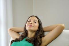 Giovane donna sorridente con canottiera sportiva verde che si rilassa su un sofà a casa che si siede su un sofà nel salone Fotografie Stock Libere da Diritti
