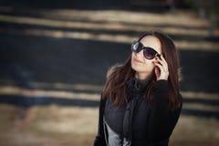 Giovane donna sorridente con gli occhiali da sole Fotografia Stock