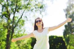 Giovane donna sorridente con gli occhiali da sole in parco Fotografia Stock