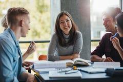 Giovane donna sorridente con i compagni di classe in biblioteca Immagini Stock Libere da Diritti