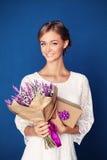 Giovane donna sorridente con i fiori ed il regalo Fotografie Stock