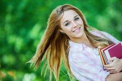 Giovane donna sorridente con i libri Fotografia Stock