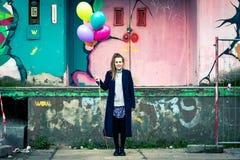 Giovane donna sorridente con i palloni variopinti all'industriale urbano b Fotografia Stock
