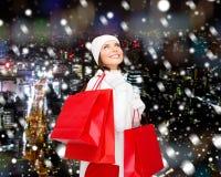 Giovane donna sorridente con i sacchetti della spesa rossi Immagini Stock
