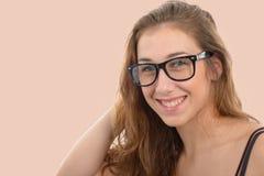 Giovane donna sorridente con i vetri neri, su fondo rosa-chiaro Immagine Stock