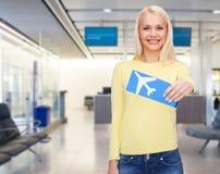 Giovane donna sorridente con il biglietto di aeroplano Immagini Stock Libere da Diritti