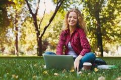 Giovane donna sorridente con il computer portatile all'aperto Immagine Stock Libera da Diritti